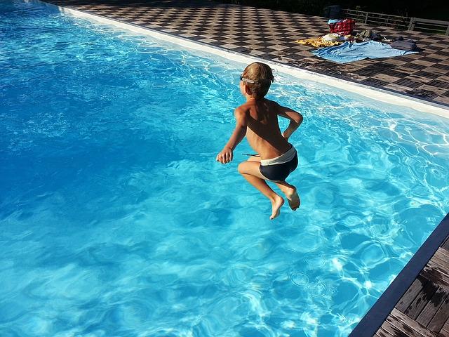 dítě jak skáče do bazénu