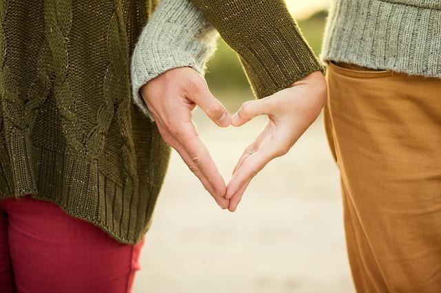 pár ona a on se drží za ruce a vytvářejí rukama srdce.jpg