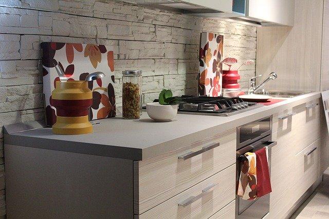 bílá kuchyňská linka s kamenným obkladem nad pracovní deskou